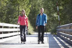 Germany, Upper Bavaria, Couple having nordic walk on bridge - stock photo