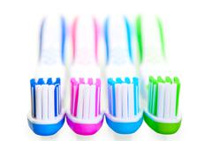 Four new multi-colored toothbrushes are on a white background Stock Photos