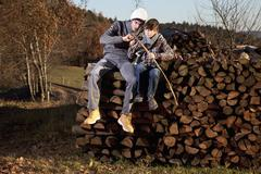 Stock Photo of Germany, Bavaria, Father and son sitting on wood and cutting stick
