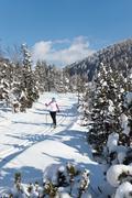 Germany, Bavaria, Aschermoos, Senior woman doing cross-country skiing - stock photo