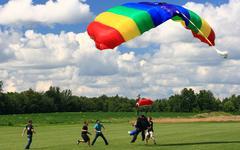 Skydivers tandem hypätä juuri ennen maata. Kuvituskuvat