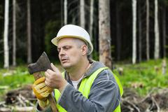 Lumberjack checking ax sharpness in forest - stock photo