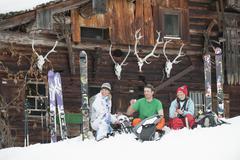 Austria, Kleinwalsertal, Friends sitting by mountain hut Stock Photos