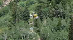 Rescue helicopter lifts load from high mountain HD 8638 Stock Footage