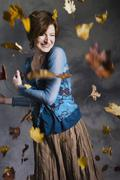 Mid adult woman having fun in falling autumn leaves Stock Photos