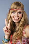 Close up of young hippie woman showing peace sign, smiling, portrait - stock photo