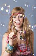 Young hippie woman with bubbles against grey background, smiling - stock photo