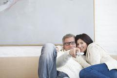 Stock Photo of Germany, Munich, Mature couple with remote control on sofa