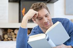 Germany, Munich, Mid adult man reading book, close up Stock Photos