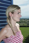 Italia, Toscana, Nuori nainen katselee ulos ikkunasta hotellihuoneessa Kuvituskuvat