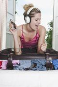 Italy, Tuscany, Young woman listening to music on top of stuffed suitcase in - stock photo