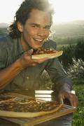 Italy, Tuscany, Young man eating pizza at dusk - stock photo
