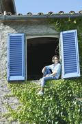 Italy, Tuscany, Young man sitting on window sill with shutters Stock Photos