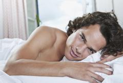 Italia, Toscana, Nuori mies makaa sängyssä hotellihuoneessa, muotokuva Kuvituskuvat