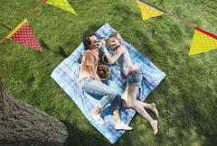 Italy, Tuscany, Young couple lying on picnic blanket with food and flag line - stock photo