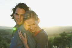 Italy, Tuscany, Young woman embracing man at dusk - stock photo