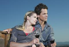 Stock Photo of Italy, Tuscany, Young couple holding wine glasses and looking away