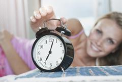 Italy, Tuscany, Young woman on bed reaching to turning off alarm clock in hotel Stock Photos