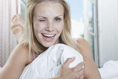 Italy, Tuscany, Young woman lying on bed in hotel room, portrait, winking - stock photo