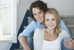 Italy, Tuscany, Young couple sitting on stairway of hotel, portrait - stock photo