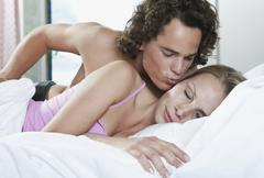 Italy, Tuscany, Young couple romancing on bed in hotel room Stock Photos