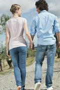 Stock Photo of Italy, Tuscany, Young couple holding hands and walking on country road