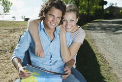 Italy, Tuscany, Young couple sitting with map at roadside - stock photo