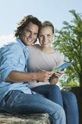 Italy, Tuscany, Young couple sitting on stone wall with map - stock photo