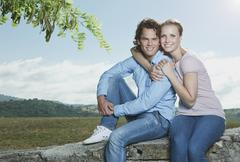 Italy, Tuscany, Young couple sitting on stone wall - stock photo