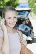 Italy, Tuscany, Close up of young woman talking on cell phone and car with - stock photo