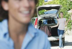 Italy, Tuscany, Close up of young man and car with luggage in background - stock photo