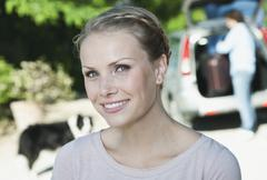 Italy, Tuscany, Close up of young woman with car and luggage in background - stock photo