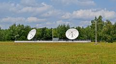 satellite antennas, green trees and thunderstorm blue sky. - stock photo