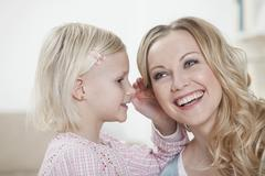 Stock Photo of Germany, Bavaria, Munich, Daughter whispering in mother's ear, smiling