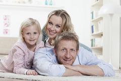 Germany, Bavaria, Munich, Family lying on carpet, smiling, portrait - stock photo
