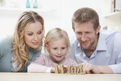 Germany, Bavaria, Munich, Parents and daughter counting coins at table, smiling Stock Photos