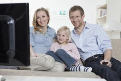 Saksa, Baijeri, München, Perhe istuu sohvalla ja katsoa televisiota, hymyilee Kuvituskuvat