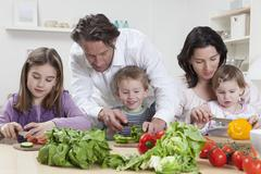 Germany, Bavaria, Munich, Mother and father helping kids to prepare salad Stock Photos