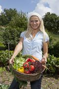 Germany, Bavaria, Altenthann, Woman with basket full of vegetables Stock Photos