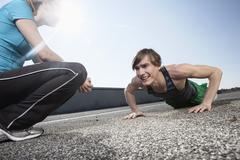 Germany, Bavaria, Munich, Young woman looking at man doing pushups - stock photo