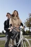 Germany, Bavaria, Munich, Young couple on bike, smiling Stock Photos