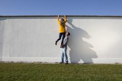 Germany, Bavaria, Munich, Young couple climbing wall - stock photo