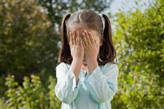 Germany, Bavaria, Huglfing, Girl playing hide and seek in garden Stock Photos