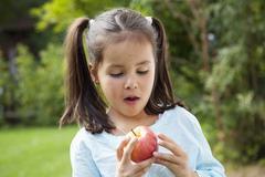 Stock Photo of Germany, Bavaria, Huglfing, Girl looking at apple, close up