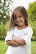 Germany, Bavaria, Huglfing, Girl with arms crossed in garden, smiling, portrait - stock photo