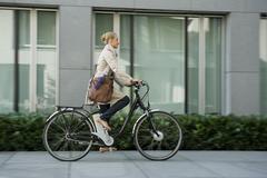 Germany, Bavaria, Teenage girl riding bicycle - stock photo