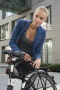 Stock Photo of Germany, Bavaria, Teenage girl fixing lock of bicycle