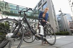 Germany, Bavaria, Teenage girl fixing lock of bicycle Stock Photos
