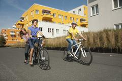 Germany, Bavaria, Man riding bicycle and girl sitting back, smiling - stock photo