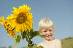 Stock Photo of Germany, Bavaria, Girl with sunflower, smiling, portrait
